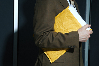Businessman carrying an envelope for corporate espionage
